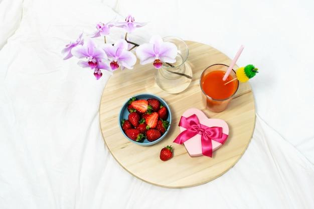 Еда и подарочная коробка с цветами на деревянном подносе