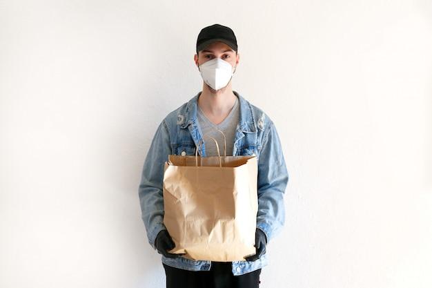 コロナウイルスのパンデミック時の食品および商品の配達。制服を着た配達員。配達員はクラフトペーパーの袋を保持しています。防護マスクとゴム手袋の男。