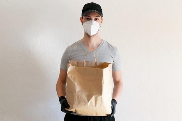 코로나 바이러스 전염병 동안 음식 및 물품 배달. 제복을 입은 배달원. 배달원이 공예 종이 봉지를 들고 있습니다. 보호 의료 마스크와 고무 장갑에 남자.