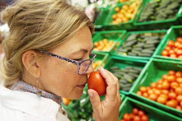 食品と健康的なライフスタイルのコンセプト。トマトを拾って、それを嗅ぐために彼女の鼻でそれを保持しているメガネで美しい高齢女性の横顔の肖像画を間近します。