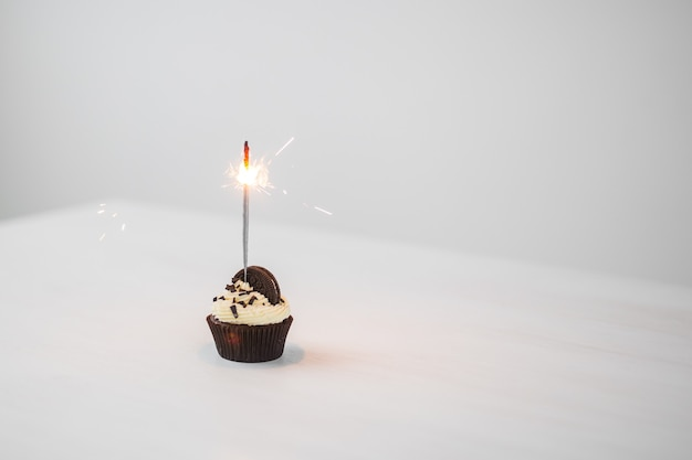Еда и концепция праздника - пирожное на день рождения с бенгальским огнем на белой стене с копией пространства.