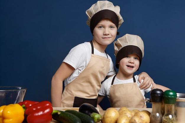 食品と栄養の概念。キッチンでポーズをとって2人の陽気な男の子の兄弟の孤立したショット