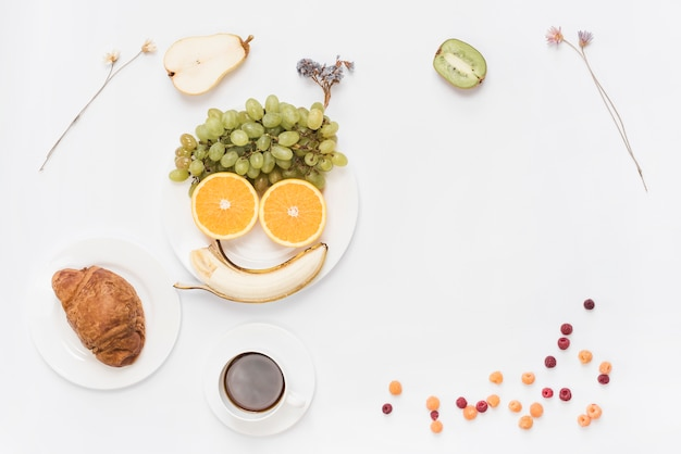 Food arranged as human face on plate with coffee; croissant and coffee on white background