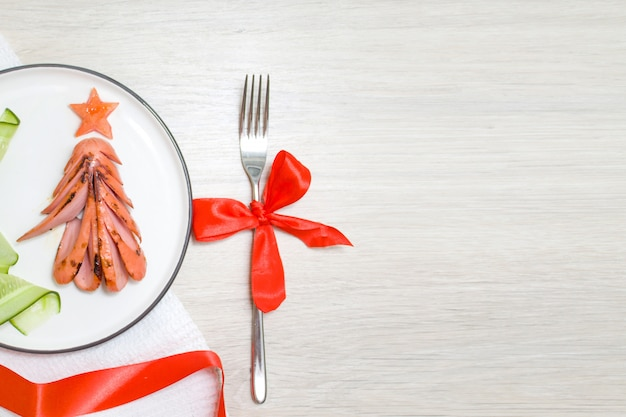 Food art concept. edible christmas tree made from fried grilled sausages, breakfast idea