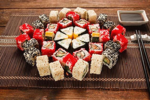 Пищевое искусство, кулинарный шедевр. большой набор суши подается в красочном орнаменте на коричневой соломенной циновке, крупным планом. фото меню роскошного ресторана.