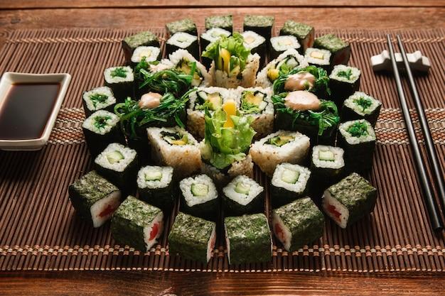 Продовольственное искусство, традиционная японская кухня. круглый орнамент зеленого набора суши-роллов служил на коричневой соломенной циновке, крупным планом. японские морепродукты, кулинарный шедевр.