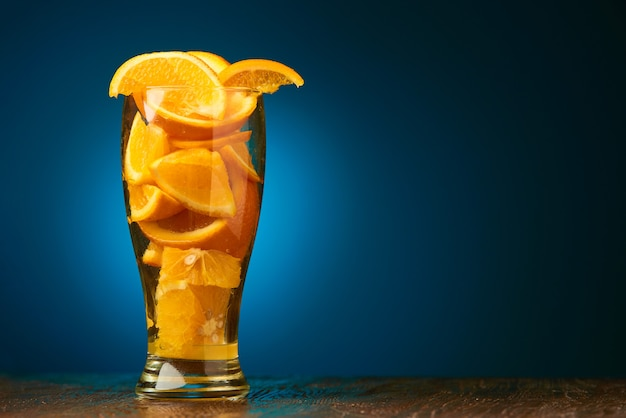 Food background  composition of orange slices in a glass on a de