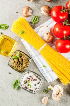 Food background ingredients for cooking dinner.  pasta spaghetti vegetables sauces and spices grey stone background