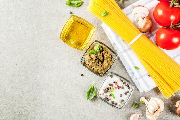 食品の背景、夕食を調理するための食材。パスタスパゲッティ、野菜、ソース、スパイス