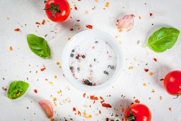 食品の背景。ランチ、ランチを調理するための材料、野菜、スパイス。新鮮なバジルの葉、トマト、ニンニク、玉ねぎ、塩、コショウ。白い石のテーブルの上。上面図