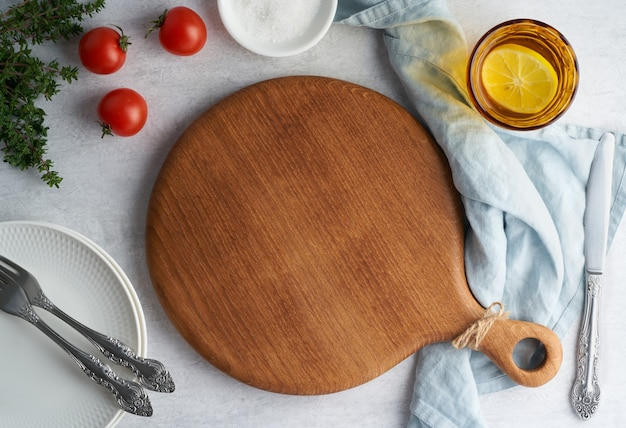 Макет продовольственного фона с круглой деревянной разделочной доской на пастельно-нейтральном сером бетонном фоне. вид сверху, копия пространства. меню, рецепт, макет.