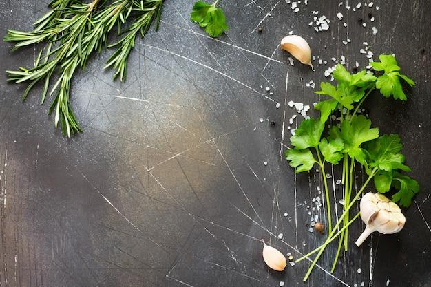 暗い石のテーブルの上の食品の背景パセリとローズマリーコピースペース上面図フラットレイ