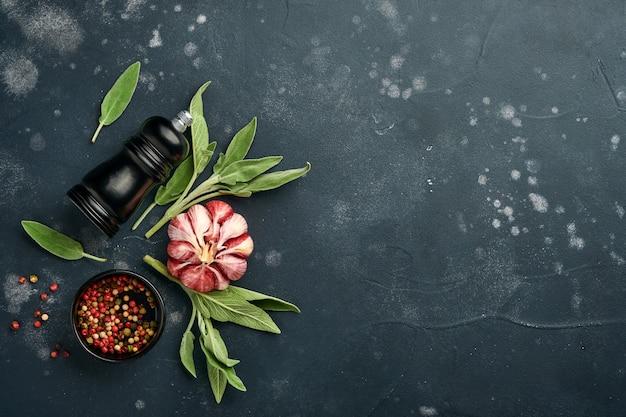 食品の背景。スパイス、ハーブ、セージの葉、色とりどりのコショウ、キッチンツール。上面図。テキスト用のスペース。素朴なスタイル。