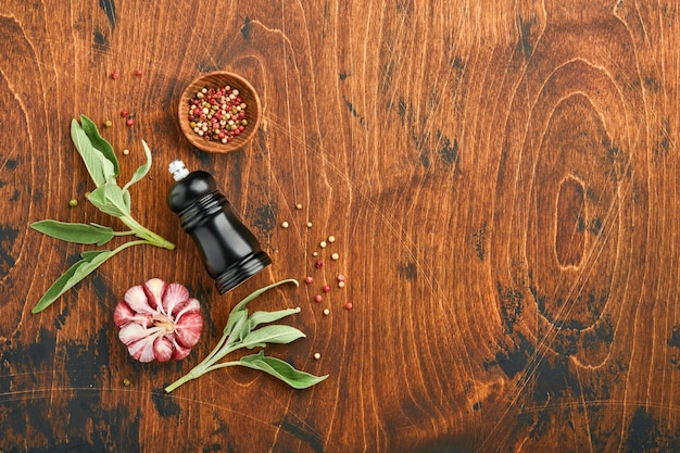 음식 배경입니다. 향신료, 허브, 샐비어 잎, 여러 가지 빛깔의 후추 및 주방 도구. 평면도. 텍스트를 위한 공간입니다. 소박한 스타일.