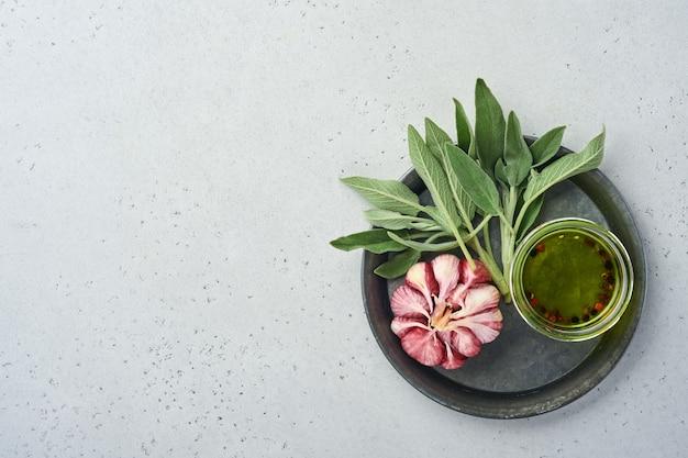 Продовольственный фон. специи, зелень, лист шалфея, разноцветный перец и кухонные принадлежности. вид сверху. место для вашего текста. деревенский стиль.