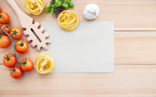 Food background for tasty italian dishes with blank brown paper and vintage pasta ladle on wooden background.