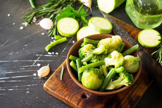 食品の背景さまざまな夏の緑の野菜スパイスオリーブオイルと新鮮なハーブ