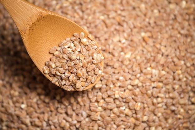 食品の背景。木のスプーンの小麦粒。上面図