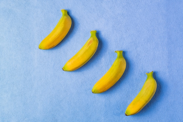 Food background with banana fruit on blue paper.