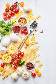 Food background with different kinds of pasta, tomatoes, herbs, mushrooms, eggs, seasonings scattered on light marble background, top view. italian cuisine concept