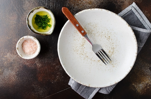 Food background with empty plate, napkin, fork and spices on a dark stone or concrete background.