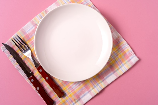 Food background with empty white plate, cutlery and napkin, over pink