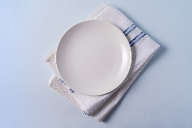 Food background with empty white plate over light blue