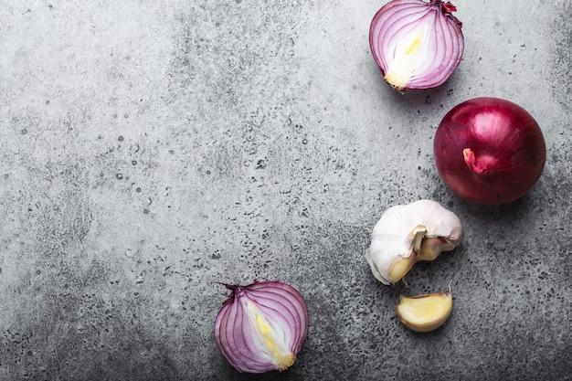 テキスト用の空きスペースがある食品の背景。素朴な灰色の石の背景、料理、ベジタリアン料理、または健康的な食事の概念にカット生の新鮮な玉ねぎとニンニクの拡大図、上面図