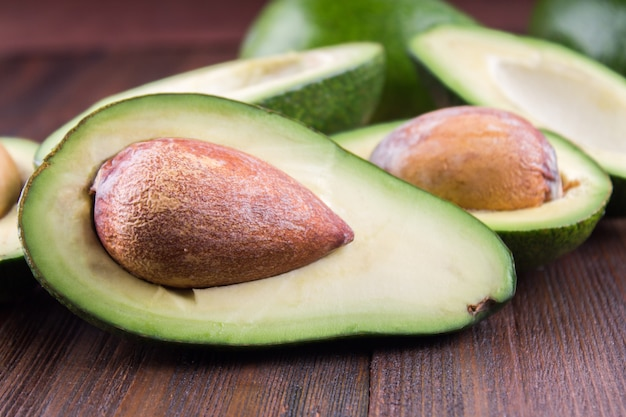 Food background with fresh organic avocado on old wooden table,