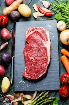 Food background with fresh vegetables and raw beef steak