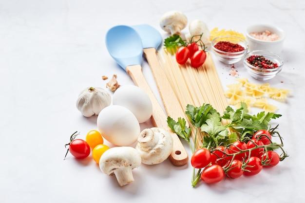 밝은 대리석 배경에 흩어져있는 파스타, 토마토, 허브, 버섯, 계란, 조미료의 다른 종류와 텍스트를위한 장소가있는 음식 배경. 이탈리아 요리 컨셉