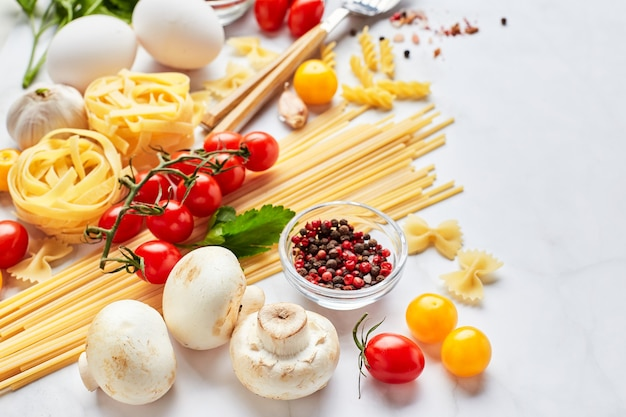Food background with place for text, with different kinds of pasta, tomatoes, herbs, mushrooms, eggs, seasonings scattered on light marble background. italian cuisine concept