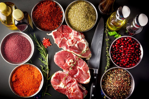 Food background with raw meat ribeye steaks and seasoning