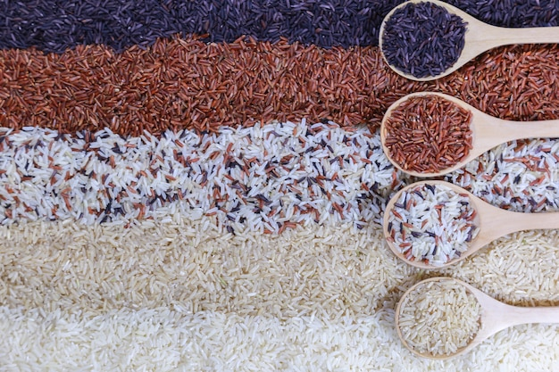 Food background with top view of five rows of rice in a wooden spoon.