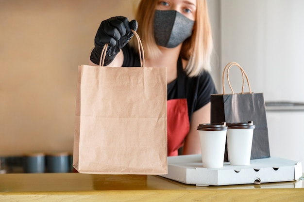 Food bag, pizza, drink package to go in takeaway restaurant. kitchen worker issues online orders in gloves and mask. takeaway food paper bag. contactless food delivery lockdown covid 19.
