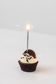 食品、パン屋、休日、お誕生日おめでとう、デザートのコンセプト-白いテーブルに線香花火とクッキーとおいしいカップケーキ