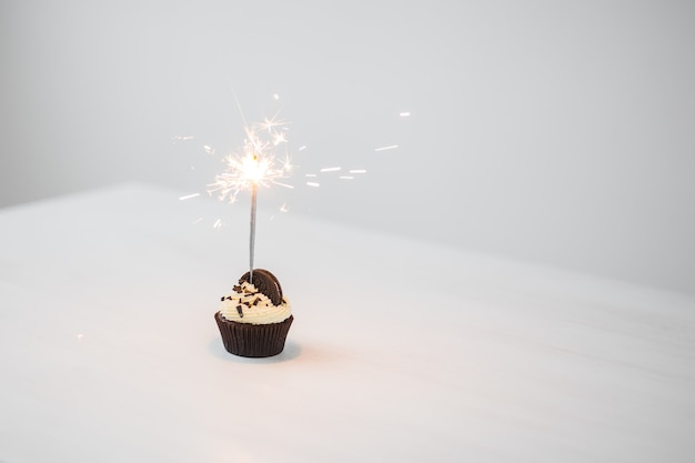 Food, bakery, holiday, happy birthday and desserts concept - delicious cupcake with sparkler and