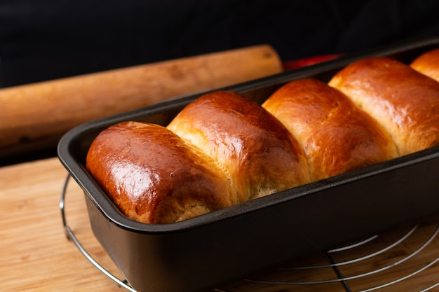 Food baking concept fresh baked organic homemade soft milk loaf bread in loaf pan on wooden board with copy space