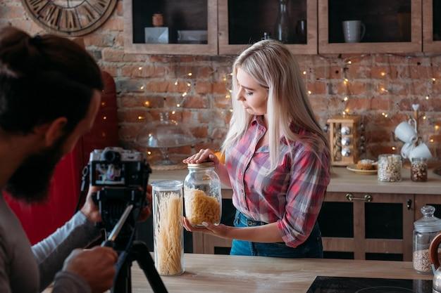 음식 블로거. 조언. 여성 라이프 스타일. 요리 팟 캐스트. 파스타의 항아리와 젊은 여자를 촬영하는 사람
