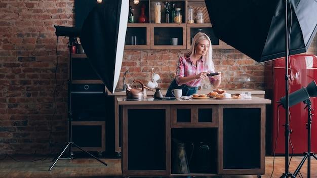 음식 블로거. 백 스테이지 사진. 여성 취미와 생활 방식. 파이를 촬영하는 스마트 폰으로 젊은 여자.