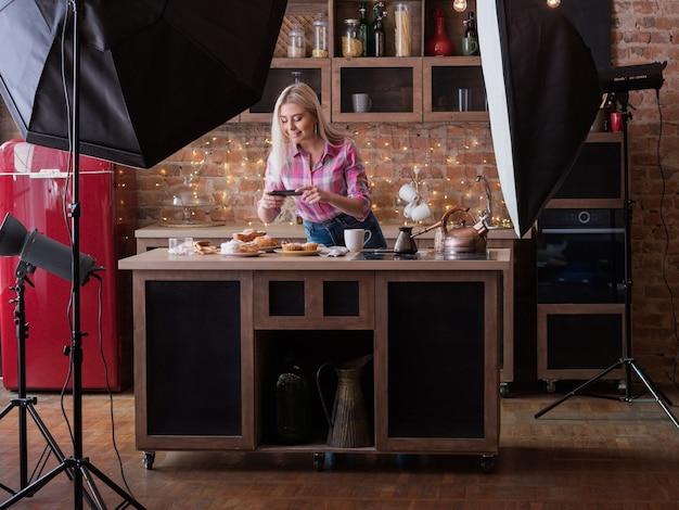 음식 블로거. 백 스테이지 사진. 여성의 라이프 스타일과 비즈니스. 파이를 촬영하는 스마트 폰으로 젊은 여자.