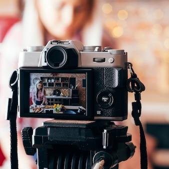 음식 블로거. 카메라 장비. 로프트 주방에서 동영상 블로그 에피소드를 기록하는 젊은 금발의 여자.