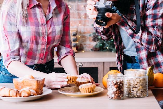 음식 블로거. 디저트 구색. 신선한 머핀의 여자와 남자 복용 사진입니다. 수제 파이, 견과류와 과일 항아리.