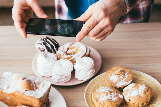 음식 블로거. 디저트. 모바일 사진. 신선한 홈 메이드 파이의 사진을 찍는 스마트 폰으로 남자. 머랭, 과일 케이크, 머핀.