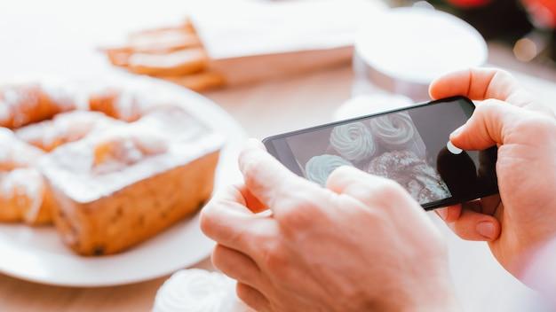 음식 블로거. 디저트. 모바일 사진. 신선한 홈 메이드 패스트리의 사진을 찍는 스마트 폰을 가진 남자