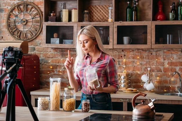 음식 블로거. 여성 라이프 스타일. 요리 팟 캐스트 촬영. 제기 검지 손가락으로 젊은 여자.