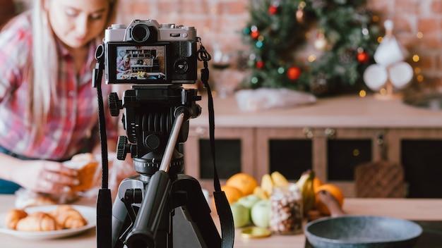 음식 블로거. 디저트를위한 과일과 생과자. 부엌에서 vlog 에피소드를 기록하는 젊은 여자.