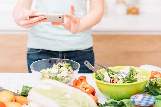 음식 블로거. 건강한 영양. 신선한 야채 샐러드 그릇. 스마트 폰으로 여성 자른 샷.