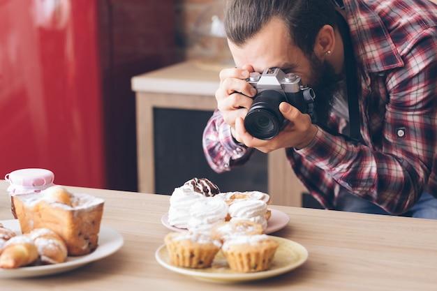 음식 블로거. 취미와 생활 방식. 케이크와 파이 구색의 남자 복용 사진.