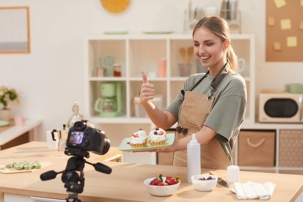 Food blogger holding baked cakes in her hands and showing thumb up to the camera while shooting the video in the kitchen